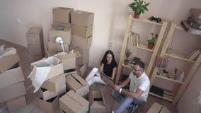 Ruszać się młodej rodziny nowy mieszkanie Mąż i żona ściskamy each inny i siedzimy na podłoga otaczającej pudełkami i zbiory