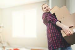 Ruszać się w nowego dom - uśmiechnięty młodej kobiety przewożenie boksuje obraz stock