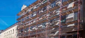 Rusztujący blisko domu w budowie dla zewnętrznie tynk prac, wysokiego budynku mieszkaniowego w mieście, biel ściany i okno, ye Fotografia Stock
