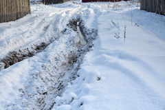 Rut with puddles. Traces of tractor tires in snow. Deep furrows Stock Images