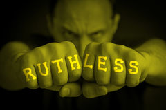 RUTHLESS written on an angry man fists. RUTHLESS written on the fingers of an angry man fists. Yellow colored. Message concept image Royalty Free Stock Photos