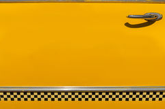 Rutig gul dörr för taxitaxi Arkivbild