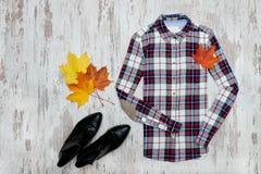 Rutig skjorta, svarta skor, lönnlöv trendigt begrepp Royaltyfri Bild
