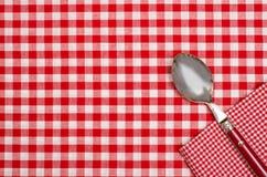 Rutig tabelltorkduk med röda och vitkontroller och en sked Fotografering för Bildbyråer