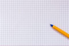 Rutigt papper och penna Arkivfoto