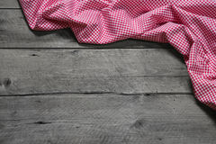 Rutigt tyg som gränsen på grå träbakgrund Royaltyfri Bild