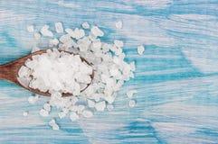 Rutina de la sal del mar en la cuchara de madera de la tabla lamentable azul clara de madera Cocina y uso sano cosmético , primer Imagenes de archivo