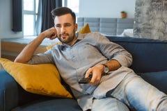 Rutina diaria del hombre del soltero en el solo concepto de la forma de vida de la sala de estar que mira programa de la TV foto de archivo