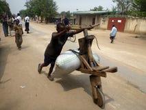 Rutshuru demokratiska Republiken Kongo: Ung pojke som skjuter hans fullastade träcykel royaltyfri foto