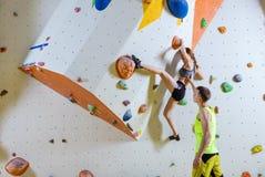 Rutt för problem för klättring för ung kvinna bouldering, manlig instruktör Arkivbilder