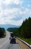 Rutten av skogen och att försvinna in i bergen Flödet av bilar Centrala Sibirien Fotografering för Bildbyråer