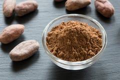 Ruw cacaopoeder, met cacaobonen op de achtergrond royalty-vrije stock foto's