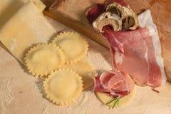 Ruw deeg en Italiaanse eigengemaakte ravioli, open en gesloten die, met paddestoelen, okkernoten en aromatische kruiden wordt gev Stock Afbeeldingen