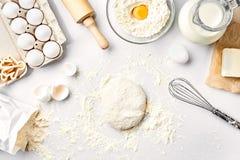 Ruw deeg klaar voor het kneden op witte lijst Bakkerijingrediënten, eieren, bloem, boter Vormen voor het maken van koekjes stock fotografie