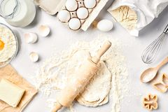 Ruw deeg klaar voor het kneden op witte lijst Bakkerijingrediënten, eieren, bloem, boter Vormen voor het maken van koekjes royalty-vrije stock afbeeldingen