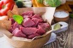 Ruw die kalfsvlees in stukken met groenten en andere ingrediënten wordt gesneden Royalty-vrije Stock Foto