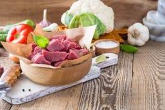 Ruw die kalfsvlees in stukken met groenten en andere ingrediënten wordt gesneden Stock Foto's