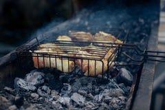 Ruw Geroosterd kippenbeen bij de grill, over steenkolen met rook Stock Afbeelding