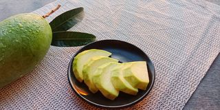 Ruw groen mangofruit op zwarte plaat Grote groene mango stock afbeelding