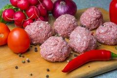 Ruw hak pasteitjes in het koken fijn de koteletten worden voorbereid op scherpe raad royalty-vrije stock foto's