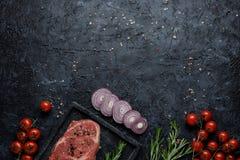 Ruw het ooglapje vlees van de rundvleesrib met tomaten, ui en rozemarijn op zwarte hoogste mening als achtergrond Met exemplaarru royalty-vrije stock foto