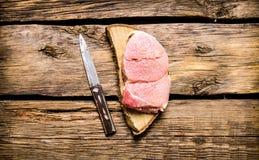 Ruw lapje vlees met een mes op een houten tribune Stock Afbeeldingen
