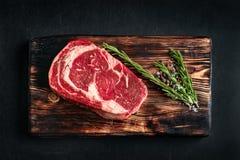 Ruw ribeyelapje vlees op een houten Raad op zwarte achtergrond royalty-vrije stock fotografie