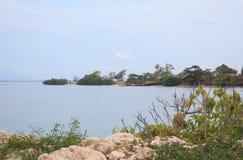 Ruw rotseiland met blauwe overzees, Eenzaamheidszonsondergang Stock Foto's
