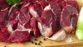 Ruw rundvlees op houten raad met knoflook en uien stock video