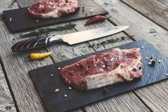 Ruw rundvleeslapje vlees op donkere houten lijstachtergrond Stock Afbeelding