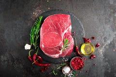 Ruw rundvleeslapje vlees op zwarte achtergrond met het koken van ingrediënten Vers rundvleesvlees royalty-vrije stock afbeeldingen