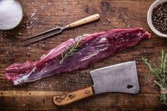 Ruw rundvleesvlees Het ruwe lapje vlees van het rundvleeshaasbiefstuk op een knipselraad met het zout van de rozemarijnpeper in a Stock Foto
