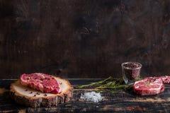 Ruw sappig vleeslapje vlees op donkere houten achtergrond klaar aan het roosteren Royalty-vrije Stock Afbeeldingen