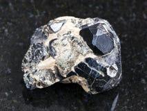 ruw Spinel kristal op zwarte Diopside kristallen stock afbeeldingen