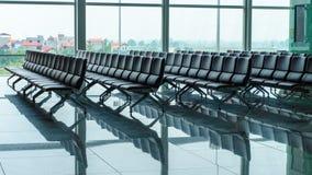 Ruw van lege zetels op luchthaven wachtend gebied dichtbij poort en groot venster stock foto's