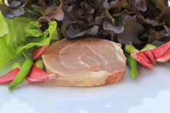 Ruw varkensvlees op scherpe raad en groenten Royalty-vrije Stock Foto's
