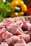 Ruw varkensvlees op scherpe raad en verse groenten Stock Afbeeldingen