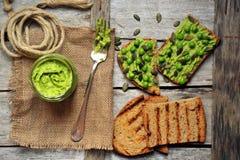 Ruw, vers alkalisch voedsel met avocado en de sandwich van erwtenpesto Stock Foto's