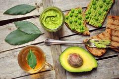 Ruw, vers alkalisch voedsel met avocado en de sandwich van erwtenpesto Stock Foto