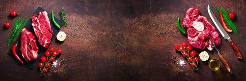Ruw vers vleeslapje vlees met kersentomaten, hete peper, knoflook, olie en kruiden op donkere steen, concrete achtergrond banner Stock Fotografie