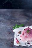 Ruw vers vleeslapje vlees met kruiden en peper op een donkere concrete achtergrond Voedselvarkensvlees Stock Fotografie