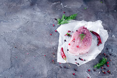 Ruw vers vleeslapje vlees met kruiden en peper op een donkere concrete achtergrond Voedselvarkensvlees Stock Foto