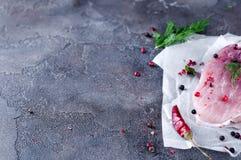 Ruw vers vleeslapje vlees met kruiden en peper op een donkere concrete achtergrond Voedselvarkensvlees Stock Afbeeldingen
