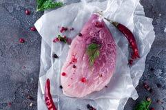 Ruw vers vleeslapje vlees met kruiden en peper op een donkere concrete achtergrond Voedselvarkensvlees Royalty-vrije Stock Foto's