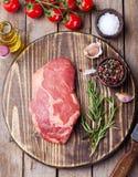Ruw vers vleeslapje vlees met zout en peper, rozemarijn en tomaten op scherpe raad op donkere houten Hoogste mening als achtergro Stock Afbeelding
