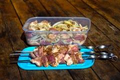 Ruw vlees, die kebab maken Vleespennen klaar voor het roosteren en stukken van varkensvlees met uipeper in container op houten li Stock Afbeelding