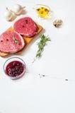 Ruw vlees met olijfolie, kruiden en rozemarijn op witte houten raad Vers rundvlees Klaar aan het roosteren Stock Afbeeldingen