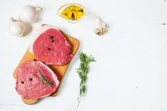 Ruw vlees met olijfolie, kruiden en rozemarijn op witte houten raad Vers rundvlees Klaar aan het roosteren Royalty-vrije Stock Foto's