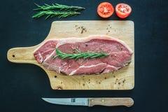 Ruw vlees op houten scherpe raad met mes Stock Foto's