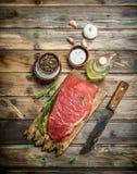 Ruw vlees Vers rundvlees op een knipselraad met kruiden en kruiden stock foto's